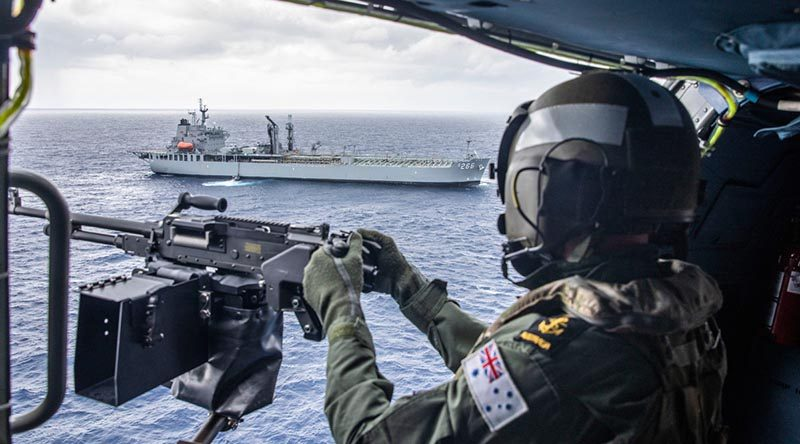 Leading Seaman Jason Griffiths mans the MAG 58 light support weapon in HMAS Stuart's MH-60R helicopter with HMAS Sirius in the background. Photo by Leading Seaman Tara Byrne.