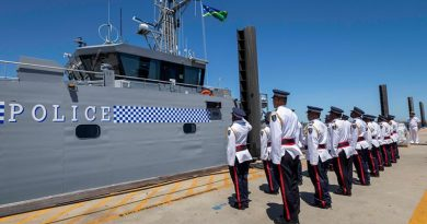 Members of the Gizo crew stand at attention while the Solomon Island national flag is raised for the first time on their new patrol boat, at Austal Shipyards, Western Australia. Photo by Leading Seaman Kylie Jagiello.