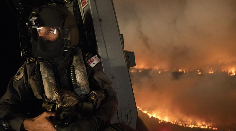 Royal Australian Navy aircrewman Leading Seaman Ben Nixon of 808 Squadron assesses a NSW national-parks bushfire from his MRH90 Taipan helicopter. Photo by Chief Petty Officer Kelvin Hockey.