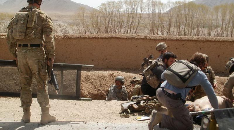 David Savage, right, lies injured on the ground after the blast that nearly killed him in the Chora Valley, Afghanistan, in 2012. Photo supplied by David Savage to the ABC.