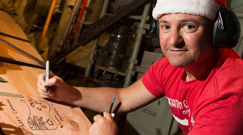 Flight Sergeant Geoff McLaughlin of Number 37 Squadron writes a message on an airdrop load destined for a Micronesian island during Operation Christmas Drop 2019. Photo by Corporal David Said.