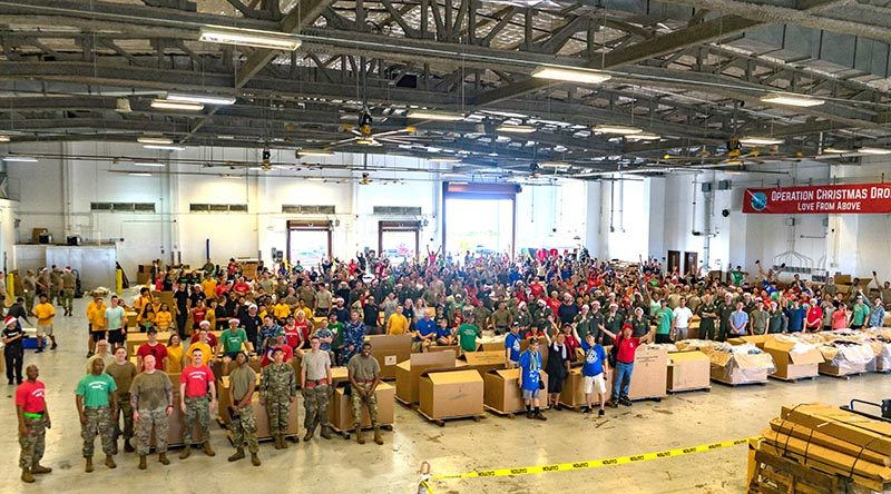 Service members and volunteers who helped build air-drop supply bundles at Andersen Air Force Base, Guam, for Operation Christmas Drop 2019. US Air Force photo by Staff Sergeant Kyle Johnson.