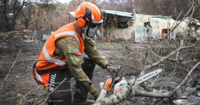 Private Jake Jubelin, an Army Reserve infantryman from the 2nd/17th Battalion, Royal NSW Regiment, cuts apart a fallen tree to restore access to a burn-out property. The owner's home (background) was destroyed by bushfire, with the elderly couple forced to share a tent until access for a new caravan was restored by the Army. Photo by Major Cameron Jamieson