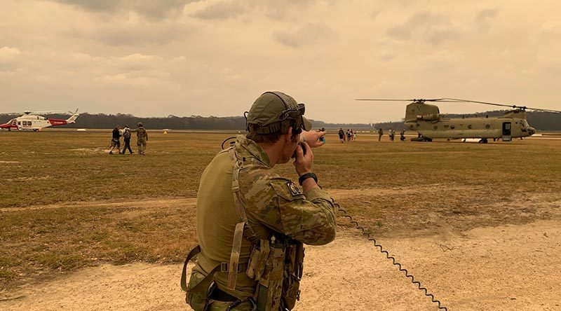 A 4 Squadron combat controller assists with the evacuation of civilians and the departure of Defence assets from Mallacoota airfield. Photo by Squadron Leader Chris Sharp.