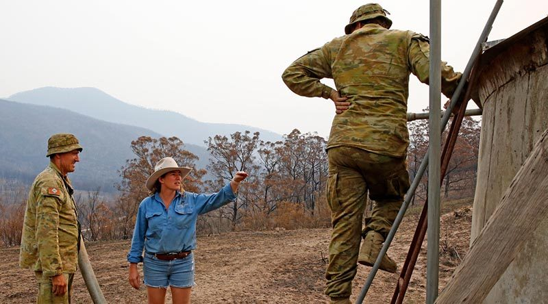 Australian Army soldiers Private Daniel Muntz (left) and Private Brendan Harvey deliver 9000 litres of water to remote-property owner Donna Thomson, who's water pump was destroyed by bushfires, leaving her, her family and her livestock dangerously short of water. The soldiers are from the Brisbane-based 7th Combat Service Support Battalion. Phot and story by Sergeant Dave Morley.
