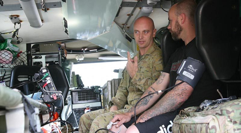 Private Brenden Walker, in a Bushmaster ambulance, gives Jay Twemlow a check-up during a health visit to Batlow, NSW. Photo by Major Cameron Jamieson.
