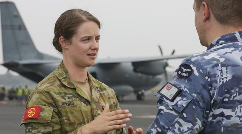 Army Corporal Ashton Brooks, from the Joint Movement Control Office, liaising with an Air Force member during the dispatch of supplies. Photo by Corporal Kylie Gibson