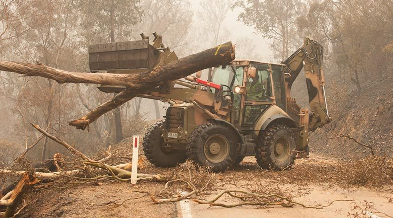 Plant operators Cpl Duncan Keith and Sapper Ian Larner of the 22nd Engineer Regiment use a 434 backhoe to assist staff from Forestry Management Victoria to clear fire-damaged trees from the Great Alpine Road between Bairnsdale and Omeo during Operation Bushfire Assist 19-20. Photo by Private Michael Currie.