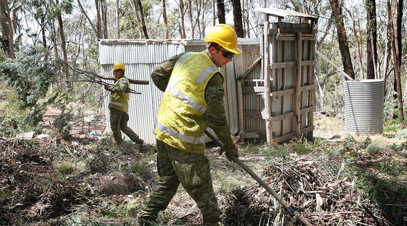 Private Ben Keogh uses a fire rake to clear vegetation away from the historic Bendora hut, located high in the Namadgi National Park in the ACT. Photo by Major Cameron Jamieson.