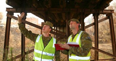 Army sappers Lance Corporal Rick Williams, left, and Corporal Ross Lorenz, of the 5th Engineer Regiment, inspect a fire-damaged bridge in Cobargo. Photo by Sergeant Max Bree.