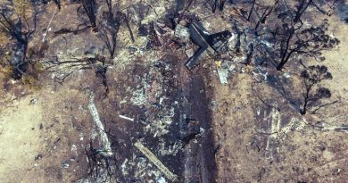 An aerial photo of the C-130 crash site, with the charred remains of the tail section at the end of a long skid uphill to its final resting place. This tail section is the largest piece of wreckage left after a very violent crash. NSW Police photo.