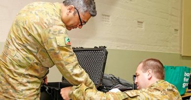 Australian Army Reserve Privates Syed Mairoj Hussainy and Aaron Clarke set up a Department of Human Services POP machine to give a mobile Centrelink disaster relief team secure online communications, at Batlow, New South Wales. Photo by Sergeant Dave Morley.
