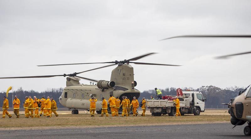 Victorian CFA firefighters arrive on an Australian Army CH-47 Chinook helicopter at Mallacoota. Photo: Corporal Nicole Dorrett.