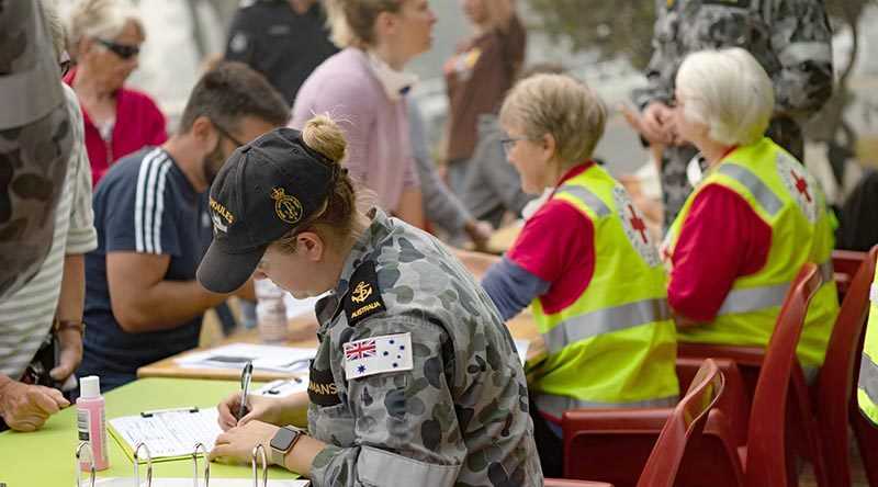 Leading Seaman Medic Abbey-Rose Yeoman and Red Cross volunteers fill out evacuation registration forms for the Mallacoota residents. Photo by Leading Seaman Shane Cameron.