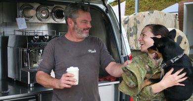 Ged Gross delivers the coffee while his Kelpie pup Tuna delivers the smiles for Captain Alisha Reeves in Bega. Photo by Major Cameron Jamieson.