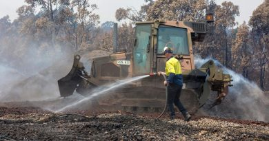 An Australian Army Combat Engineer from the 5th Engineer Regiment uses a JD-450 Bulldozer to spread burnt woodchips at the Eden Woodchip Mill in southern NSW in support of Operation Bushfire Assist 19-20. Photo by Sergeant Max Bree.