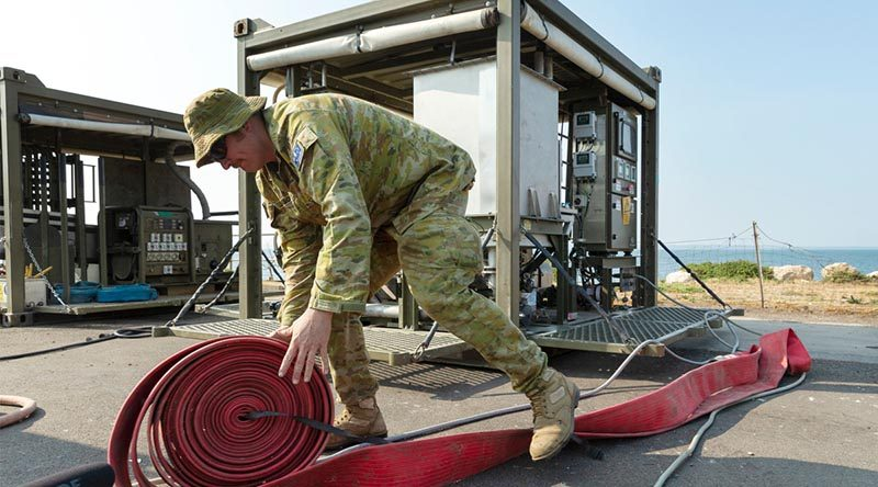Corporal Luke Jackson from the 6th Engineer Support Regiment assembles an Australian Army mobile water filtration system at the Kingscote town jetty on Kangaroo Island. The mobile plant will turn sea water into drinking water for residents of the island. Photo by Corporal Tristan Kennedy.