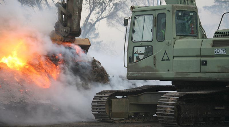 Australian Army engineers were swiftly redeployed 100km north from Cooma to Canberra in response to the Canberra fires on January 23rd. following a call from the ACT's Emergency Services Agency. A bulldozer, excavator and grader were quickly loaded onto trucks and sent forward to the emergency zone. in this photo, Sapper Mathias Beddie, from the 2nd Combat Engineer Task Group – NSW, pulls-down piles of burning mulch so that bulldozers and graders can spread it for firefighters to douse with water. The piles are too dense to extinguish without first being spread and would otherwise smoulder for weeks and remain a fire hazard. Photo by Major Cameron Jamieson.