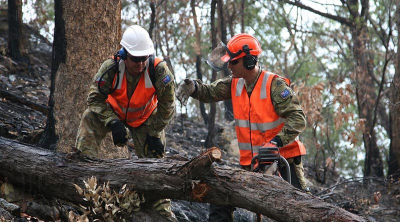 Sapper Tim Daniels, right, discusses with Sapper Aemon Kelly the best way of cross-cutting a fallen tree blocking Commission Road in Wollemi National Park south of Bulga, NSW. Photo by Major Cameron Jamieson.