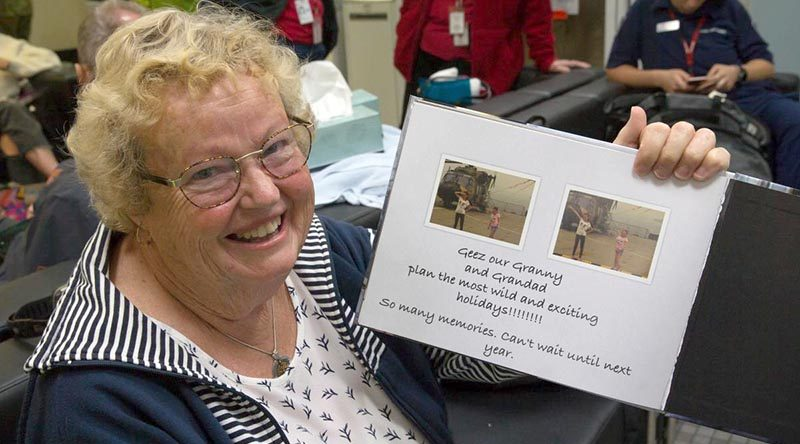 Maureen Jewell with a photo book created by her granddaughters detailing their experiences during the bushfires in Mallacoota, Victoria. Photo by Leading Aircraftman John Solomon.