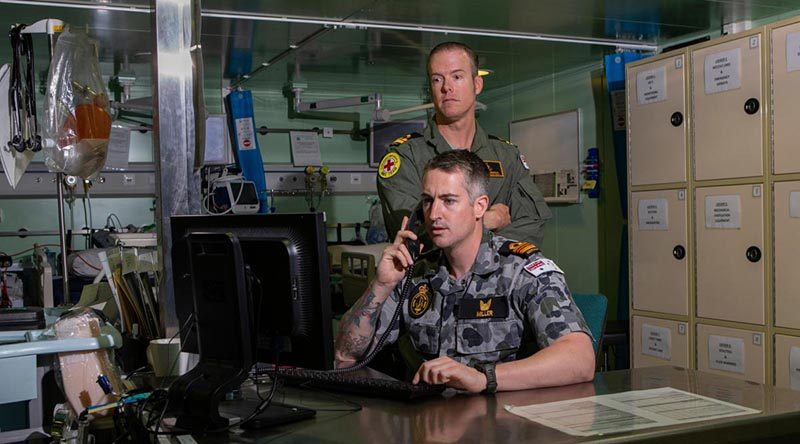 Embarked nursing officers Lieutenant Commander Thomas Miller (front) and Lieutenant Travis Robinson in HMAS Adelaide's treatment room. Photo by Able Seaman Thomas Sawtell.