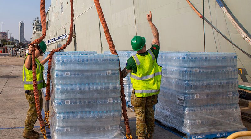 Cargo specialists Private Travis Elliot and Private Eboni Fraser load pallets of fresh water onto HMAS Adelaide at Fleet Base East, Sydney, in preparation to sailing as part of Operation Bushfire Assist 19-20. Photo by Able Seaman Benjamin Ricketts.