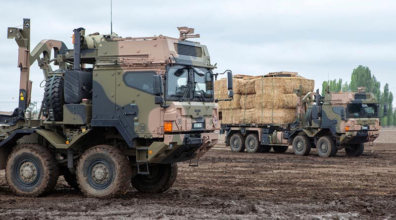 Australian Army HX77 heavy rigid vehicles load up with fodder near Cooma, NSW, for delivery to fire-affected farms. Photo by Sergeant Brett Sherriff.