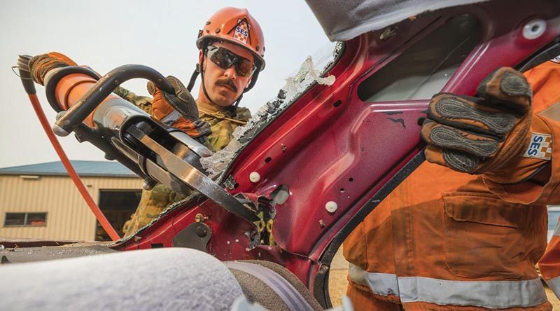 Private Andrew Cuttler, of the 5th/6th Royal Victorian Regiment, helps a State Emergency Service volunteer use the 'jaws of life' during training at the Bright SES depot. Photo by Corporal Sebastian Beurich.