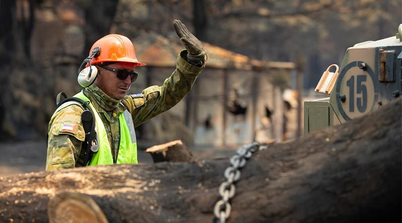 Corporal Dan Conelly, an Army Reservist from 3rd Field Squadron, 10th/27th Battalion, Royal South Australia Regiment, works to remove a burnt tree from a farm's access road on Kangaroo Island. Photo by Corporal Tristan Kennedy.