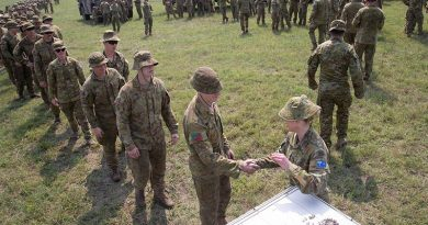 Lieutenant Colonel Renee Kidson, commanding officer of the 5th Engineer Regiment Task Group, hands out lapel pins to soldiers at the old Bega racecourse. The task group's mission was to relieve fire-affected communities and assist civil response on the New South Wales south coast from Nowra to the Victorian boarder. Photo by Sergeant Max Bree.