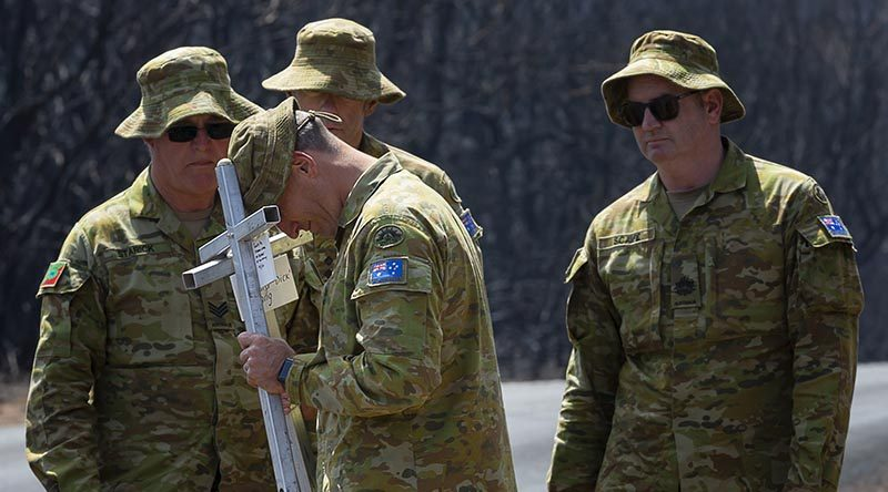 Lieutenant Kynan Lang from the 10th/27th Battalion, RSAR, is supported by colleagues at the place where his uncle and cousin died in a bushfire on Kangaroo, before placing a memorial in their honour. Photo by Corporal Tristan Kennedy.