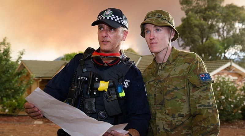 Australian Army soldier Private Lleyton Jones and Australian Capital Territory policeman Constable Marko Banic about to begin door knocking homes in Canberra's southern suburbs to advise residents on the status of the Orroral Valey fire burning in the Namadgi National Park. Photo by Sergeant Max Bree.