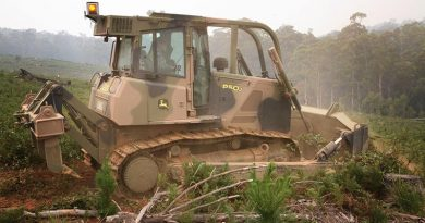 Bulldozer operator Leading Aircraftswoman Natasha Radford uses a JD 850J bulldozer to build a fire containment line at Bando Forest near Tumut to help protect remaining commercial timber essential to the economic viability of the region. Photo by Major Cameron Jamieson.