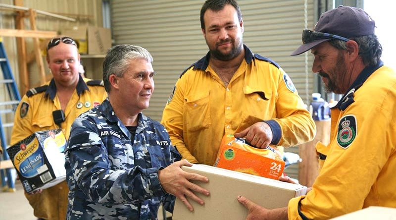 Corporal Shane Watts from 65 Squadron delivers meals and soft drinks to RFS volunteers in the fire grounds. Photo and story by Major Cameron Jameison.