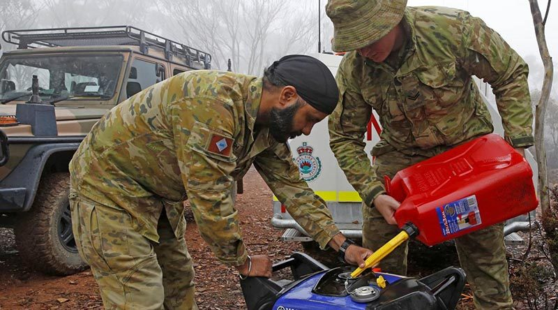 Private Manpreet Singh and Corporal Luke Ford of the Brisbane-based 7th Combat Services Support Battalion refuel a generator that powers a remote and vital RFS radio-relay antenna. Photo by Sergeant Dave Morley.