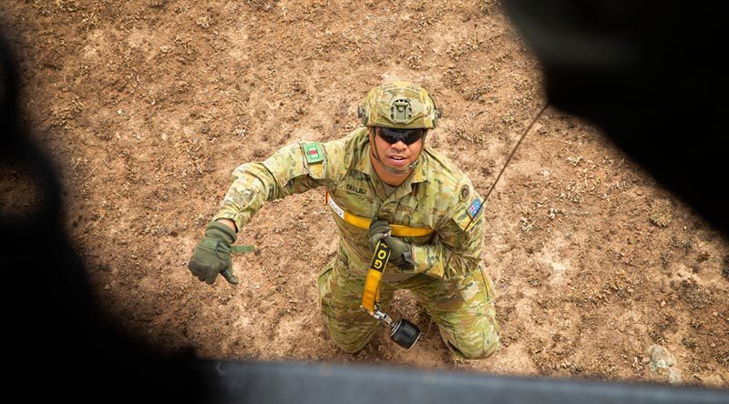 Australian Army Private Tauiliili from the 7th Battalion, Royal Australian Regiment, signals he is secure and ready to be winched up to a New Zealand Air Force NH90 helicopter in Canberra during Operation Bushfire Assist 19-20. Photo by Major Cameron Jamieson.