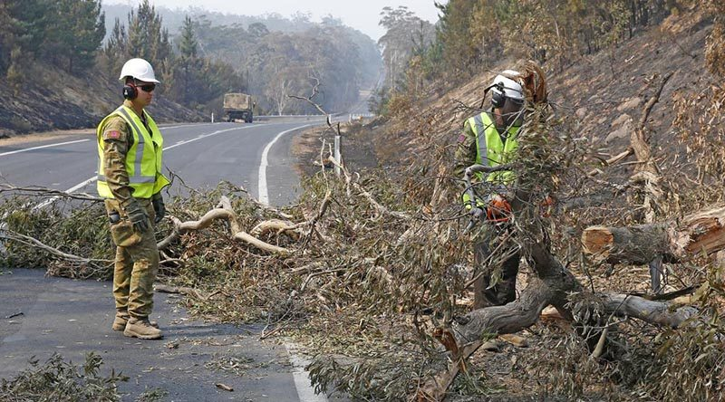 Sappers Kane Sorrell (on chainsaw) and David Mercuri from Brisbane-based 2 Squadron, 2nd Combat Engineer Regiment, help make the Monaro Highway safe. Photo by Sergeant Dave Morley