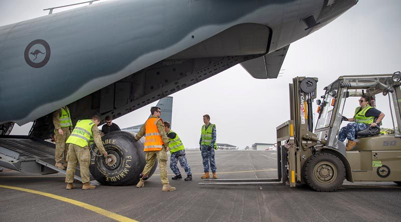 Australian Army and Royal Australian Air Force personnel work together to load a diesel fuel bladder to for Mallacoota power station onto a RAAF C-27J Spartan at RAAF Base East Sale during Operation Bushfire Assist 19-20. Photo by Corporal Nicole Dorrett.