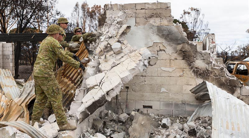 Soldiers from the 12th/40th Royal Tasmanian Regiment knock over a damaged wall of a home destroyed by bushfires on Kangaroo Island. Photo by Lance Corporal Brodie Cross.
