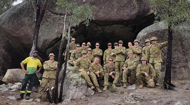 Soldiers from 6RAR with ACT Parks and Conservation Service Aboriginal field officer Kie Barratt at one of the important heritage sites they helped protect from recent bushfires. Photo by Lieutenant Jack Membrey.
