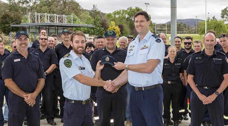 ADFA Director Education and Training Group Captain Jeff Howard presentsQueensland Fire and Emergency Services officer Sam Eitz with an ADFA cap as a token of friendship before ADFA's firefighter-guests left for home. Photo by Corporal Dan Pinhorn.