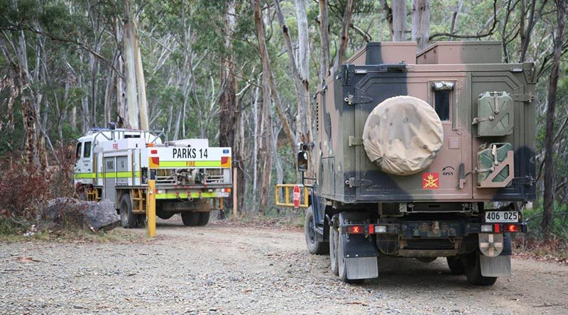 An Australian Army G-Wagon six-wheel-drive ambulance follows an ACT fire truck onto Mt Franklin Road for the drive to the edge of the Orroral Valley fire. Photo by Major Cameron Jamieson.