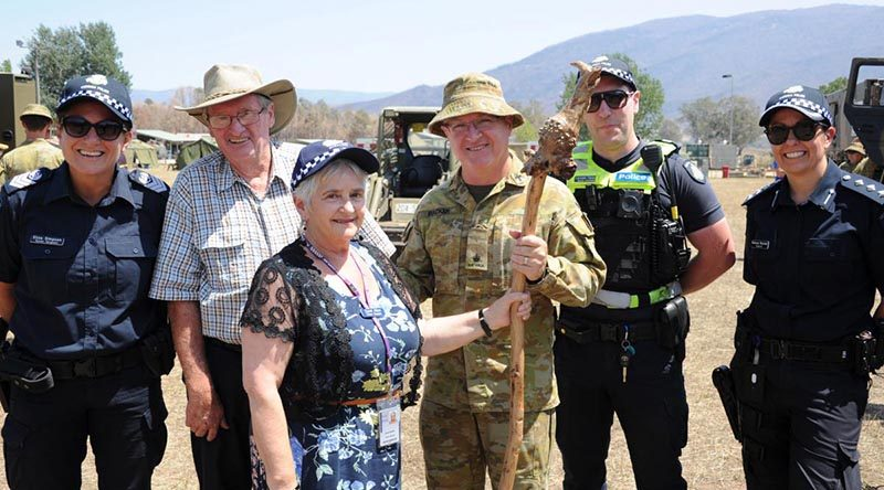 Police Chaplain Carol Allen presents the shepherd's crook to Chaplain Robert Packer, flanked by Ian Post, second from left, and members of Victoria Police. Photo by Private Stuart Rayner.