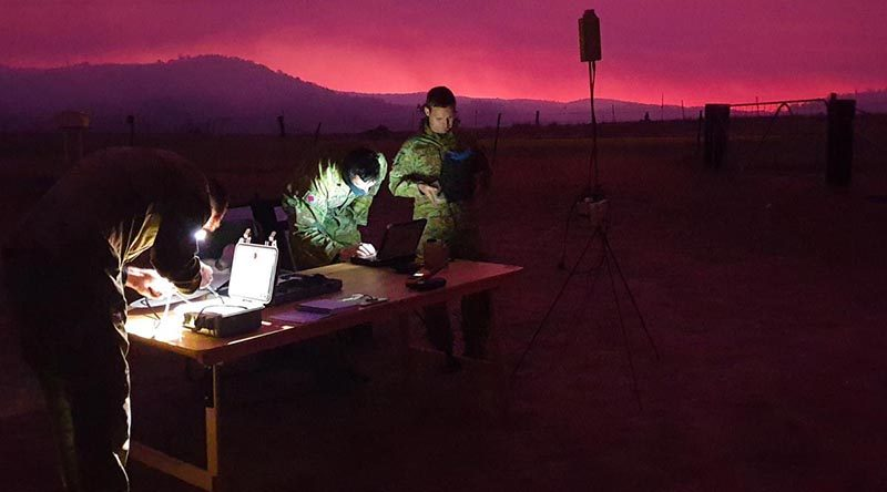 Royal Australian Artillery soldiers gather around their workstation as they guide their AE Wasp III Small Unmanned Aircraft System over the Orroral Valley fire in the south of the ACT. Photo: Captain Shaun Montgomery