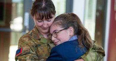 Corporal Marie Yorston and her niece, Allee, hug after their surprise reunion on her first day of high school. Photo by Private Michael Currie.
