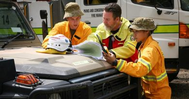Ambulance Commander Joel Powell (centre), from the ACT Ambulance Service, discuss firefighting operations with Lance Corporal Matt Fegeleson, while Lance Corporal Jessica Zhang monitors emergency services radio traffic, in the Brindabella Ranges. Together they form a remote-area ambulance team, using a six-wheel drive Army G-Wagon ambulance, to support an ACT Rural Fire Service strike team operating in remote woodlands. Photo by Major Cameron Jamieson.