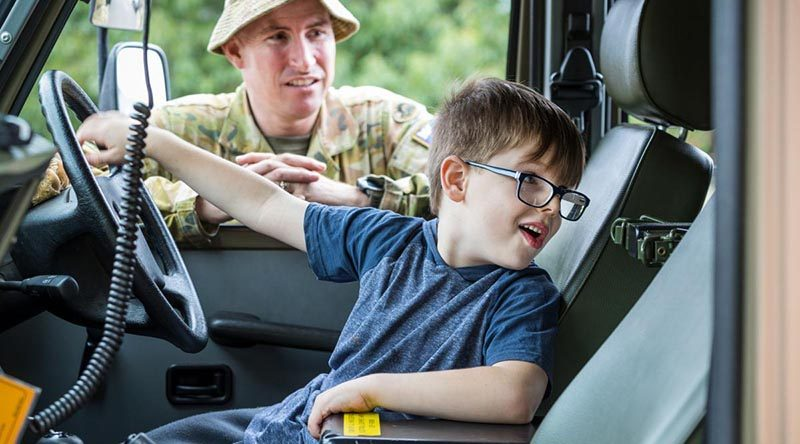 Regimental Sergeant Major 5th/6th Battalion, Royal Victorian Regiment, Warrant Officer Class One Anthony Jones watches as Omeo local Ryan checks out a Mercedes G-Wagon. Photo by Corporal Sebastian Beurich.