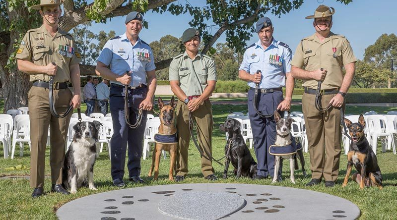 Australian Army Sergeant Stuart Conlin with Trip, RAAF Leading Aircraftman Gregory Chance with Veda, New Zealand Army Lance Corporal Maylin Broderick with Flicka, RAAF Leading Aircraftman Bradley Evans with Ollie and Australian Army Sapper Luke Saxton with Mate, at the new Military Working Dogs Memorial in Canberra. Photo by Leading Seaman Kylie Jagiello.