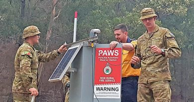 Privates Will Asquith and Aaron Smith help former Army major now NSW Rural Fire Service member Nick Sheply (centre) to set up a NSWRFS portable automatic weather station at Belowra on the New South Wales south coast.