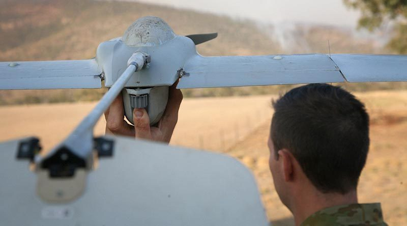 Gunner Scott Fressand, 20th Regiment, Royal Australian Artillery, prepares to launch a Wasp III drone. The aircraft is being used to monitor spot fires in the Tharwa, ACT, area in the early morning when helicopters are not operating. Integrated into the massive ACT Emergency Services Agency's intelligence collection capabilities, the small reconnaissance aircraft is fitted with an infrared video camera, ideal for looking at bushfires. Photo by Major Cameron Jamieson.